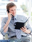Stock Photo of Serious businessman planning an appointment on phone