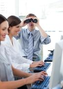 Animated businessman looking through binoculars in the office - stock photo