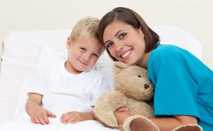 Smiling female doctor with her patient holding a teddy bear Stock Photos