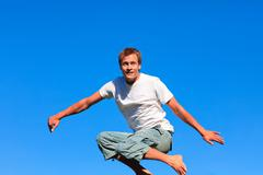 Self-assured man jumping against a blue background - stock photo