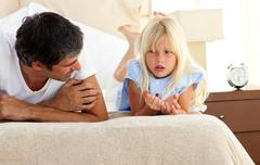 Little girl talking seriously with her father - stock photo