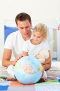 Attentive father and his daughter looking at a terretrial globe Stock Photos