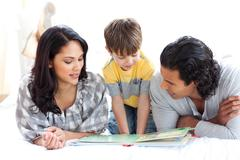 Affectionate family reading book together - stock photo