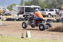 Man powerful ATV races on dirt track 1248.jpg - stock photo