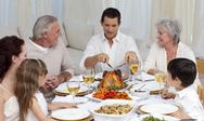 Stock Photo of Father serving turkey to his family in a dinner