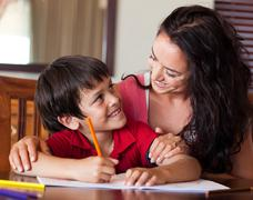 Radiant mother helping his son for homework - stock photo