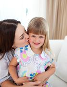 Attentive mother kissing her little girl - stock photo