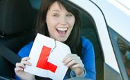 Happy brunette teen girl sitting in her car tearing a L-sign Stock Photos