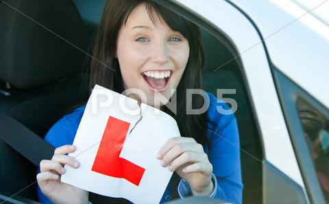 Stock photo of Happy brunette teen girl sitting in her car tearing a L-sign