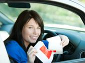 Charming brunette teen girl sitting in her car tearing a L-sign Stock Photos