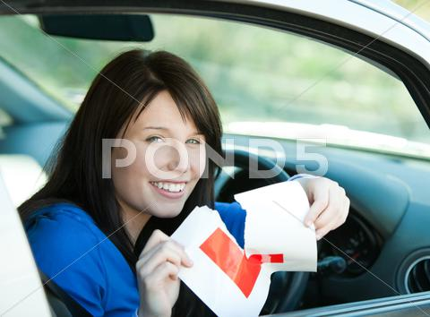 Stock photo of Charming brunette teen girl sitting in her car tearing a L-sign