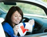 Brunette teen girl sitting in her car tearing a L-sign Stock Photos