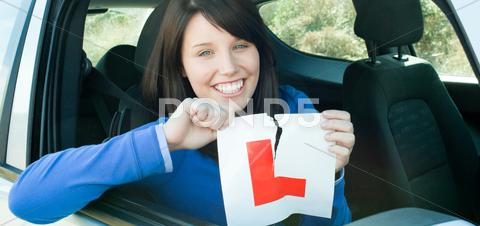 Stock photo of Smiling teen girl sitting in her car tearing a L-sign