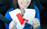Charming teen girl sitting in her car tearing a L-sign Stock Photos