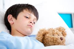Portrait of a sick boy lying in a hospital bed Stock Photos