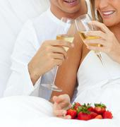 Close-up of a couple drinking Champagne with strawberries - stock photo