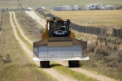 Caterpillar driving to make fire breaks during wildfire 0596 Stock Photos
