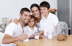 Happy family eating biscuits and drinking milk - stock photo