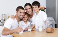 Stock Photo of Happy family eating biscuits and drinking milk
