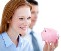 Self-assured businesswoman holding a piggybank - stock photo