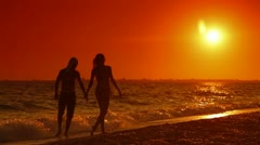 Couple Walking Along Summer Beach at Sunset Stock Footage
