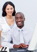 Smiling businesswoman and her colleague working at a computer Stock Photos