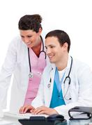Self-assured doctor and nurse working at computer - stock photo