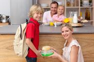 Attentive mother packing the school lunch to his son Stock Photos