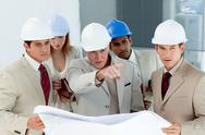 Stock Photo of Serious architect looking at blueprints and pointing