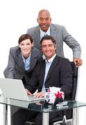 Self-assured business team working at a computer - stock photo