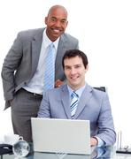 Smiling manager assisting his colleague at a computer Stock Photos