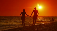Couple Walking Along Summer Beach at Sunset - stock footage