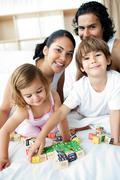 Young family having fun with alphabetics blocks - stock photo