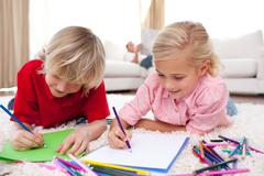Concentrated children drawing lying on the floor - stock photo