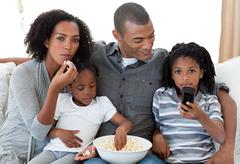 Family watching a film at home - stock photo