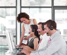 Smiling female leader managing he team in a call center Stock Photos