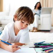 Concentrated little boy drawing and his sister eating chips - stock photo