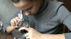 Teen girl using microscope Stock Footage