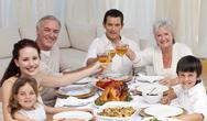 Stock Photo of Happy family tusting with wine in a dinner