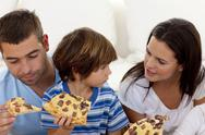 Stock Photo of Prents and son eating pizza in living-room