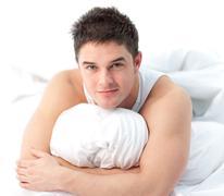 Stock Photo of Man lying on bed awake