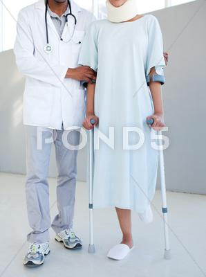 Stock photo of A physical therapist helping a patient with neck brace and on crutches