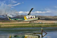 Helicopter fire fighting attack filling water bucket 0546.jpg Stock Photos