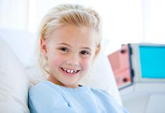 Sick little girl sitting on a hospital bed - stock photo