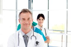Confident young female doctor smiling at the camera Stock Photos