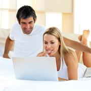 Stock Photo of Assertive woman using a laptop lying on bed