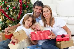 Happy family holding Christmas gifts Stock Photos