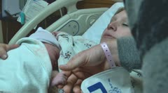 Newborn baby on mom's chest dad holds hand in hospital Stock Footage