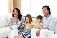 Stock Photo of Concentrated family watching TV on sofa