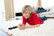Stock Photo of Concentrated boy watching TV lying on the floor
